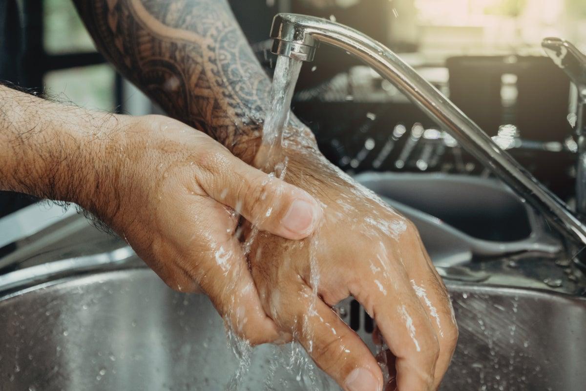 Lavado de un brazo para cuidar del tatuaje.