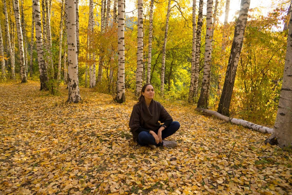 Mujer medita sentada en el suelo.