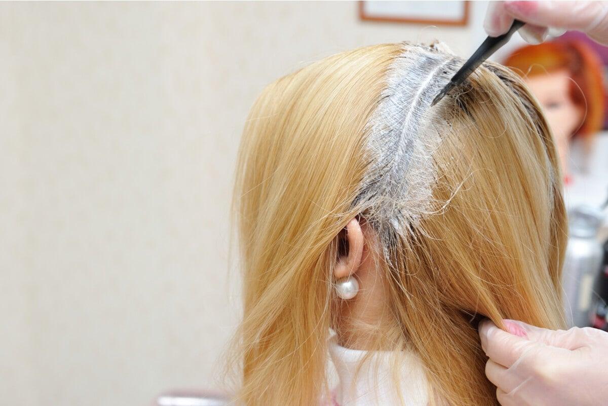 Mujer consulta con un peluquero para evitar errores al decolorar el cabello.