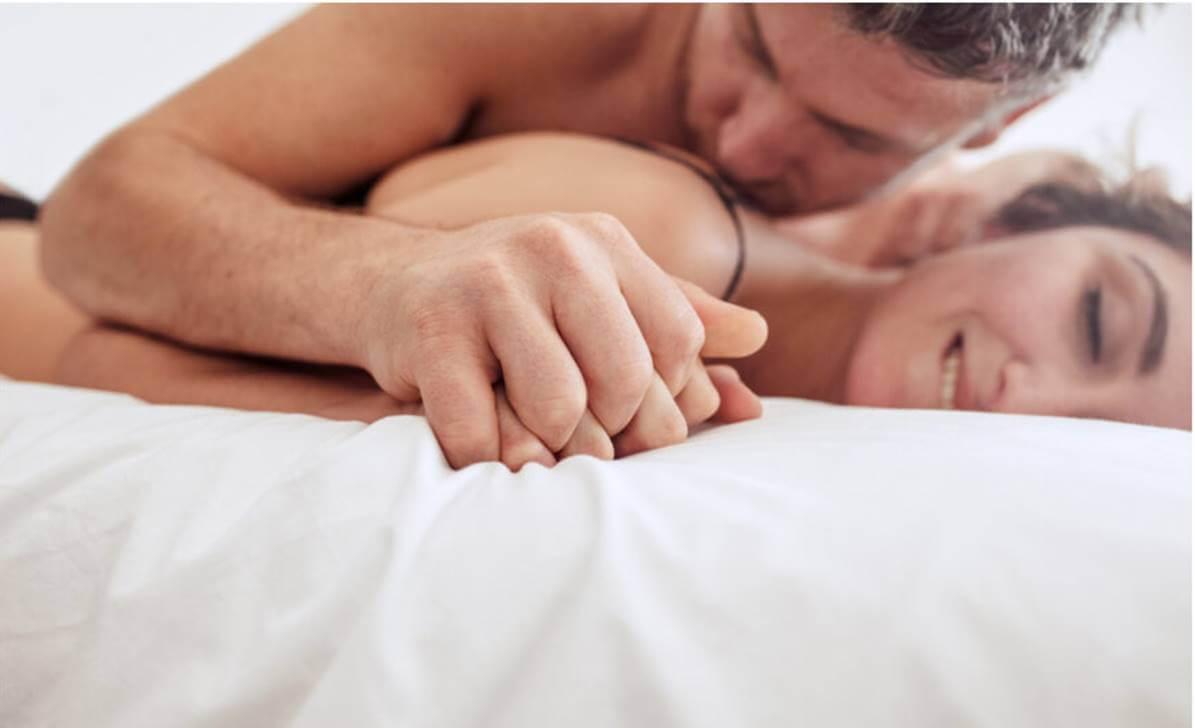 Pareja en la cama teniendo sexo.