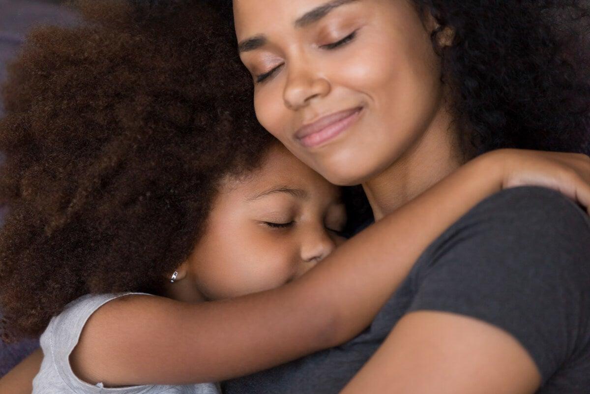 Madre abraza a una niña.