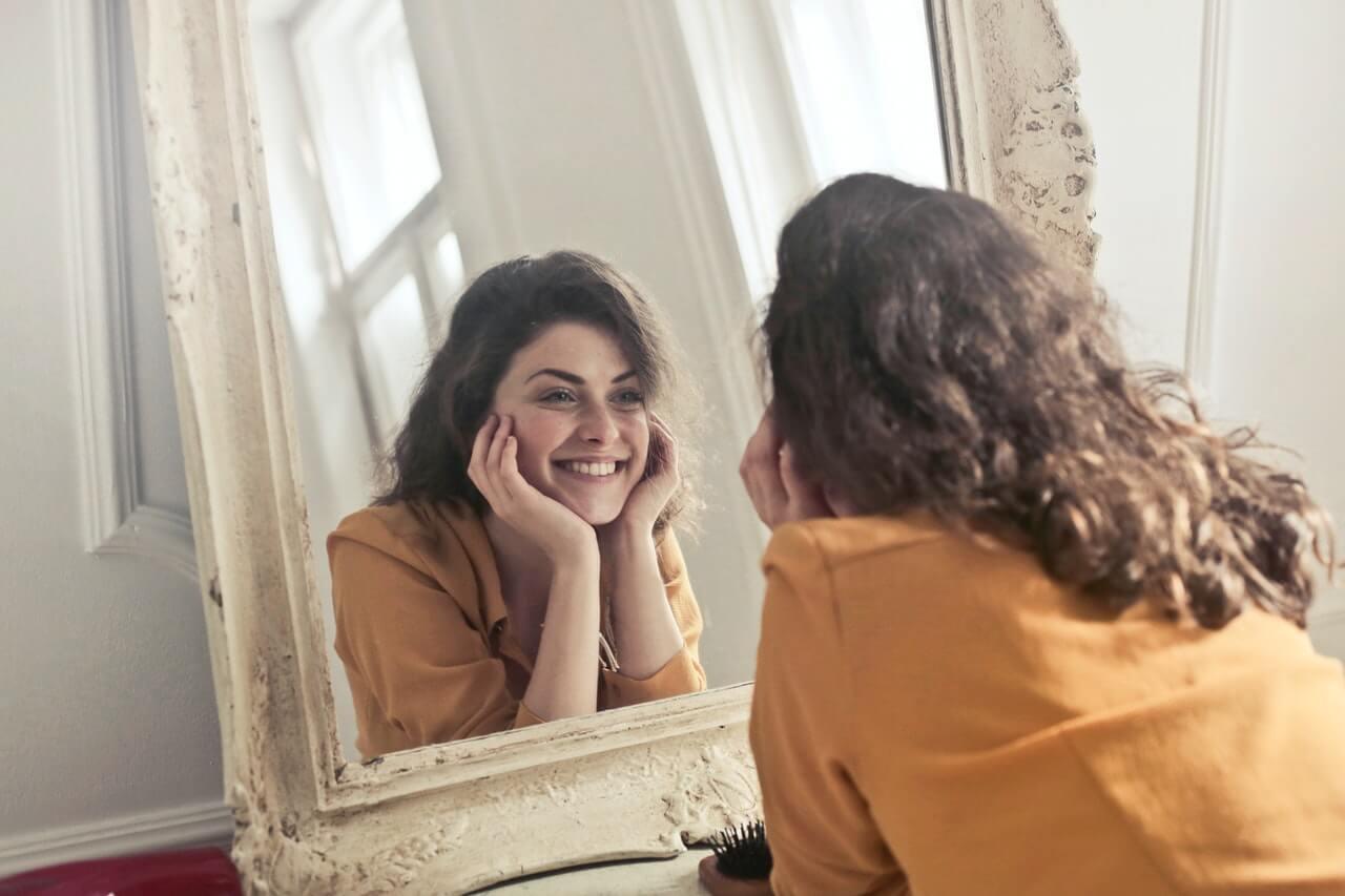 Mujer expresa gratitud frente a un espejo.
