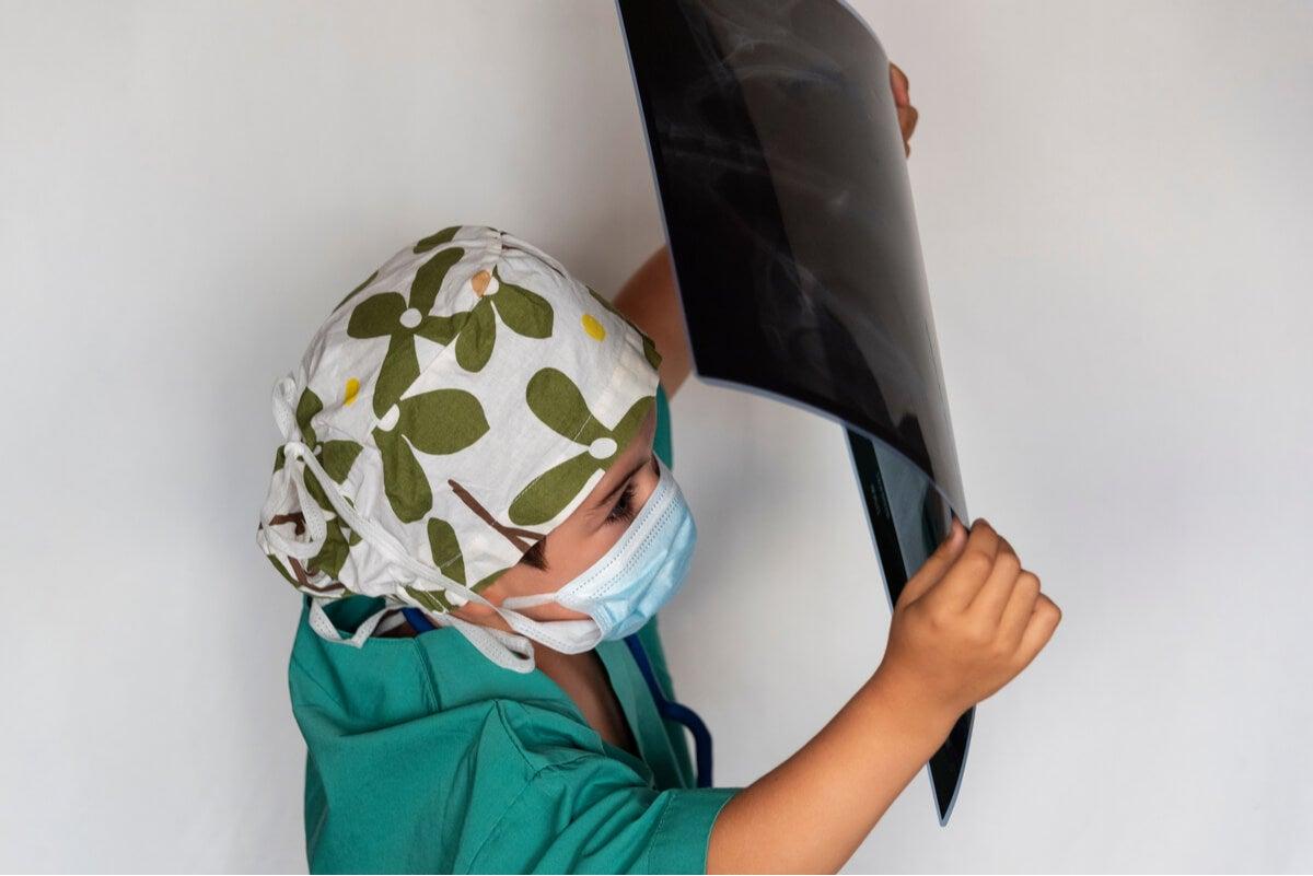 Niño con cáncer infantil juega con una radiografía.