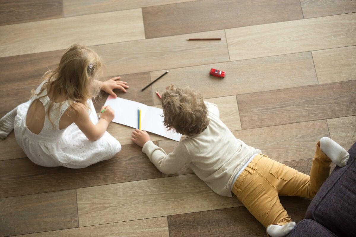 Niños rayan piso de madera.