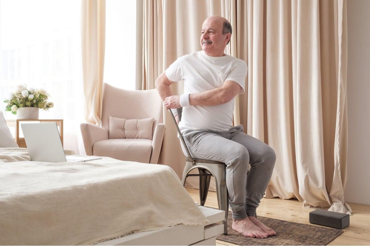 Ejercicio de yoga en silla para un adulto mayor.