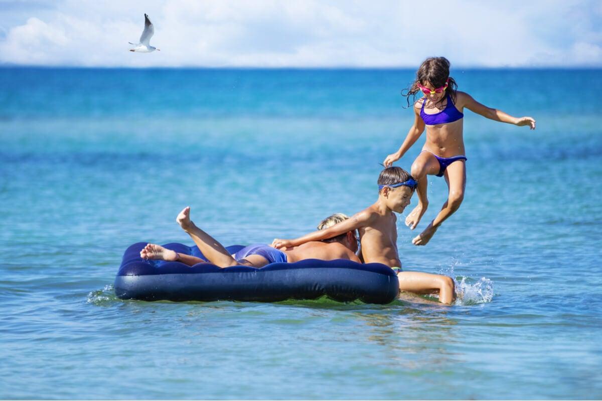 Niños juegan en colchón inflable en el agua.