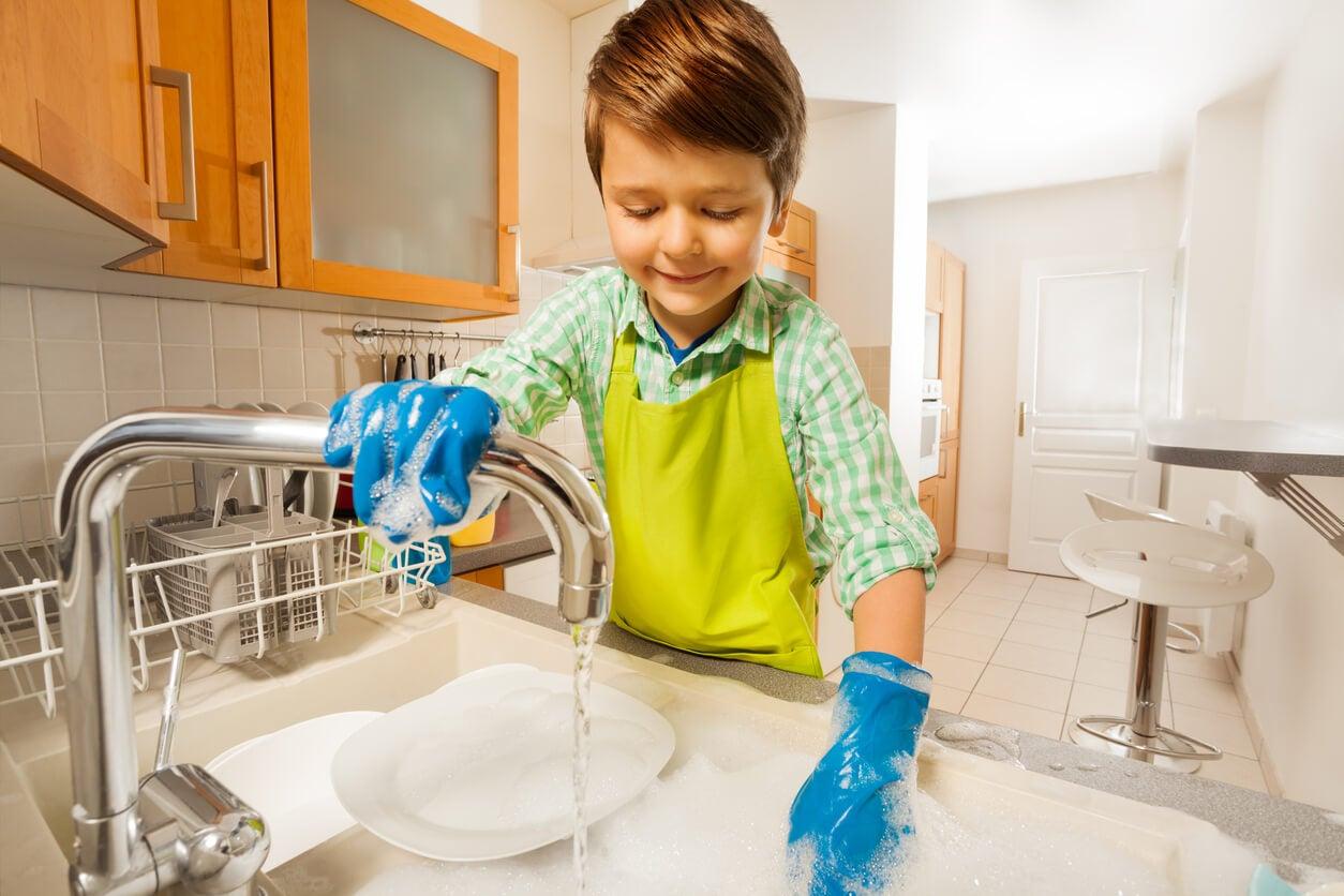 Niño lava los platos con autonomía e independencia.
